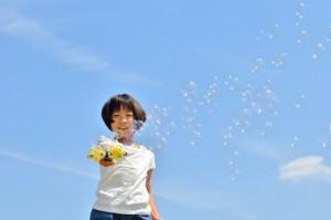 青空でシャボン玉遊びをする女の子