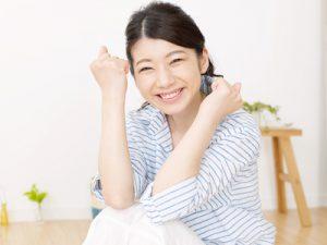 ガッツポーズで微笑む女性