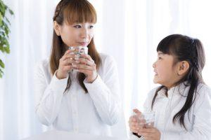 コップの水を飲む母親と娘